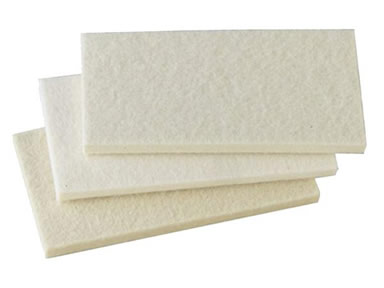 Three rectangular felt furniture pads on the white background.