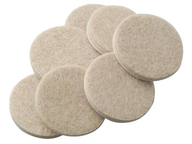 Seven round felt furniture pads on the white background.