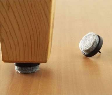 A gray wool felt nail is installed on the table leg and two another wool felt nails on the floor.