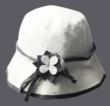 A natural white cloche hat with a flower decoration on it.