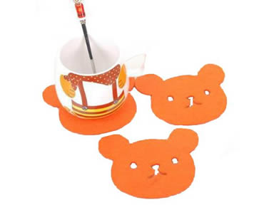 Three orange bear shaped wool felt coasters with a cup and a spoon on the one coaster.