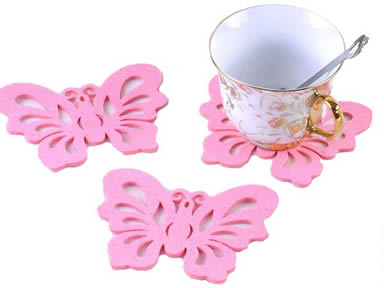 Three pink butterfly shaped wool felt coasters with a cup on the one coaster.