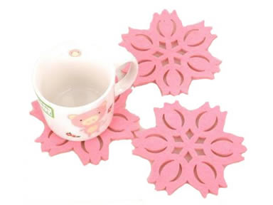 Three pink flower shaped wool felt coasters and a cup on the one coaster.