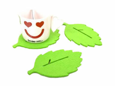 Three green leaf shaped wool felt coasters with a cup and a spoon on the one coaster.