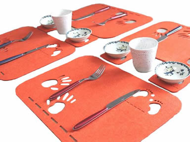 Four pieces of orange wool felt placemats with knives and folks on them and four pieces of coasters with cups and saucers on them.