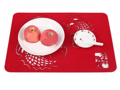 A plate with two apples and a saucer with a spoon are placed on a red fish design wool felt placemat.