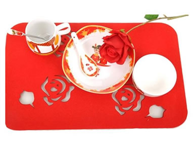 A plate with a spoon, a bowl, a cup with a spoon and a rose on the red rose design wool felt placemat.
